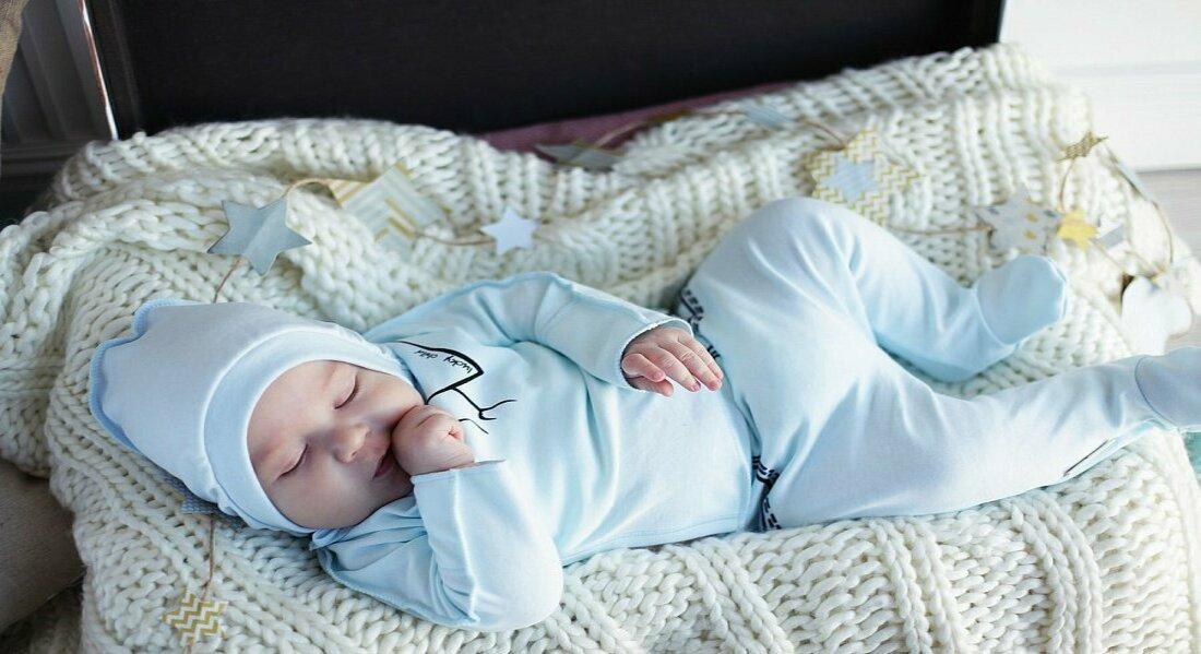 новорожденный в голубой одежде на бежевом пледе